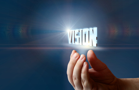Hand supports the word vision on a blue background.
