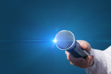 Female hand with microphone on blue background.