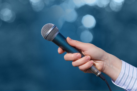 Hand of a businesswoman with a microphone on blurred background. Stock Photo