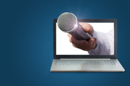 Hand with microphone for interviews from the laptop.