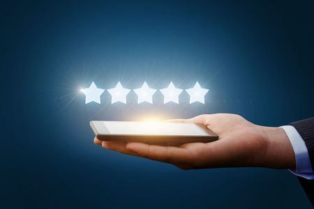 hotel reviews: Five stars from a tablet in the hands businessman.