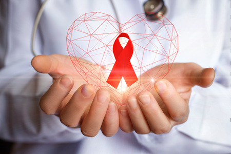 Ribbon for the fight against AIDS in the hands of the doctor. Stock Photo