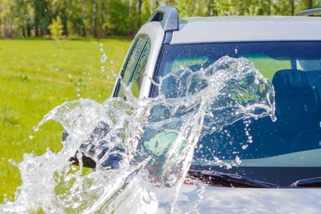 Car rinsed with water on a grass background. Stock Photo
