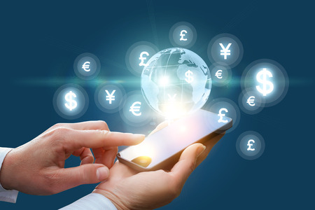 Work in the global financial market via mobile device. 스톡 콘텐츠