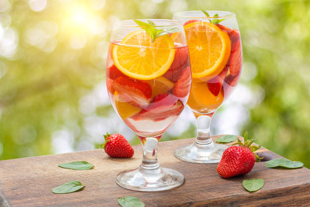 infused: Strawberry lemonade with oranges on blurred background. Stock Photo