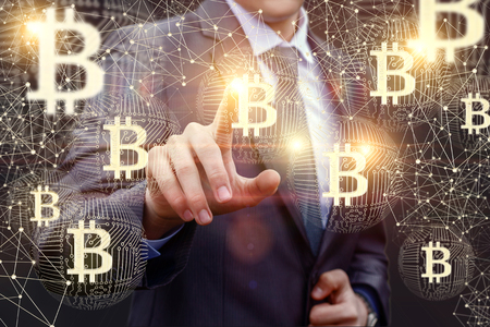 Businessman clicks on the symbol of bitcoin. Stock Photo