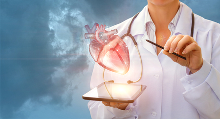 A cardiologist demonstrates the heart of man on the tablet.