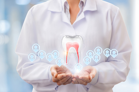 Tooth and patients in the hands of a dentist on a blue background. Stock Photo