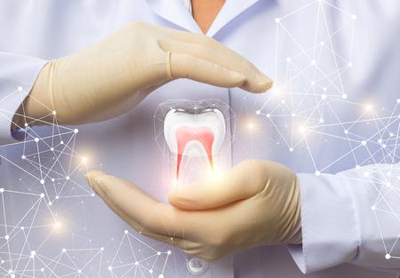 Ondersteun de tandheelkundige gezondheid. De dokter, met een gebaar van de bescherming van de tand.