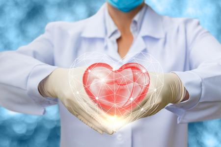 Doctor with heart in hands on blurred background. Stock Photo