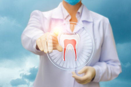 whiten: The dentist presses the tooth against the sky. Stock Photo