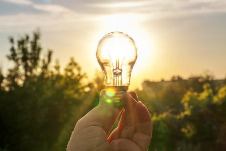 夜明けに対する手の電球。記号、新しい創造的なビジネスのアイデアの概念です。エコ エネルギー保存