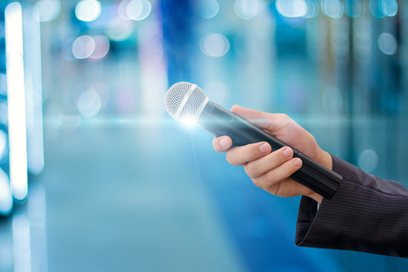 Hand of a businessman with a microphone on blurred background. Stock Photo