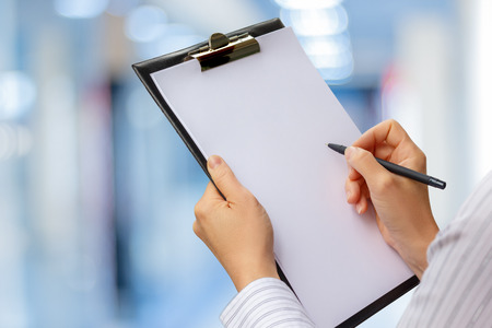 Checklist in the hands of a businesswoman on a blurred background.