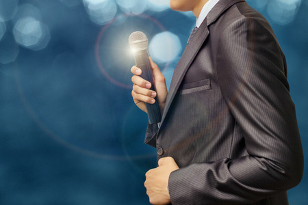 reportage: Businessman with microphone on presentations on blurred background. Stock Photo