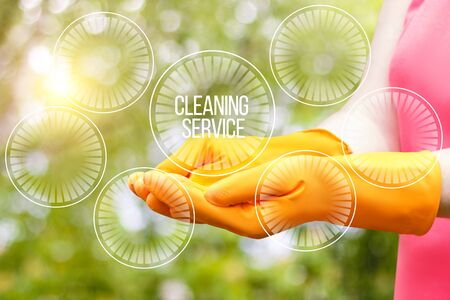 Worker showing cleaning service on blurred background. Stock Photo