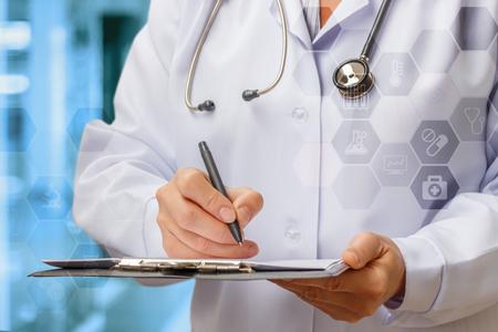 Doctor writes a prescription for the blue background. Archivio Fotografico