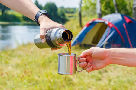 Tea is poured into a mug at the camp in the nature.