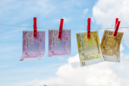 Euro banknotes weigh on the rope as linen against the sky. Stock Photo