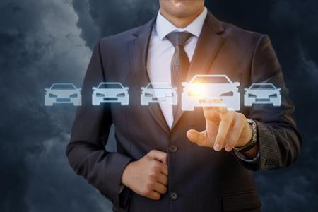 El hombre de negocios selecciona un coche sobre un fondo azul.