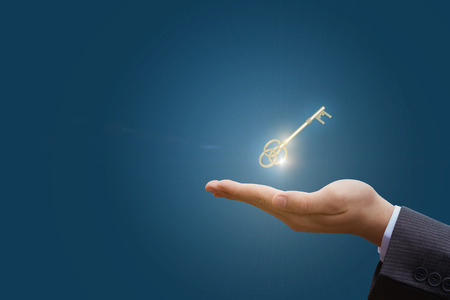 In hand the key to success in business on a blue background.