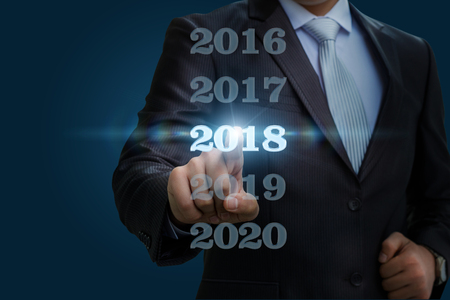 Businessman chooses 2018 on a blue background.
