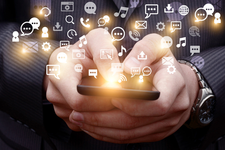 smartphone: Mobile phone businessman Emits a holographic image of social media related icons.