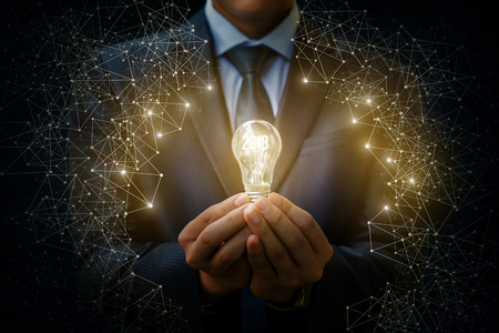 2018 light bulb as an idea in the hands of the businessman. The concept of a new year. Foto de archivo