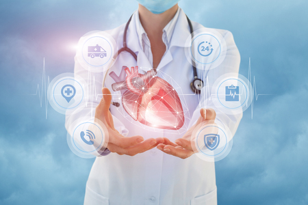 Health worker shows a heart in hands on sky background. Stock Photo