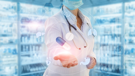 Doctor shows pill and the tablet on a blue background.