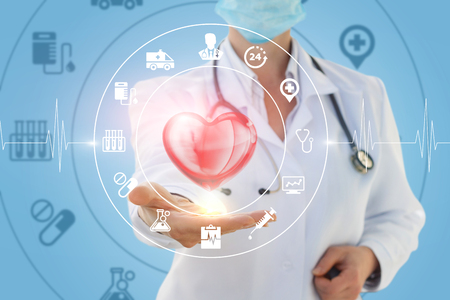 Doctor the cardiologist shows the treatment of heart on a blue background.
