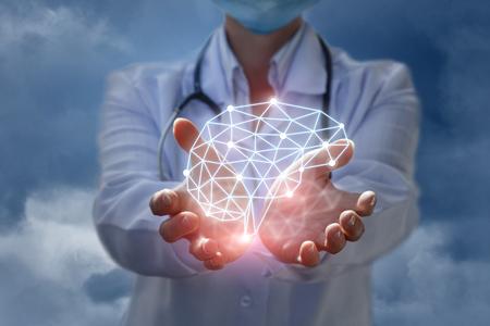 Lekarz pokazuje model myślenia mózgu w ręce na niebieskim tle. Zdjęcie Seryjne