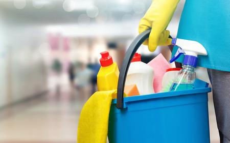 Donna di pulizia con un secchio e prodotti di pulizia su sfondo sfocato. Archivio Fotografico