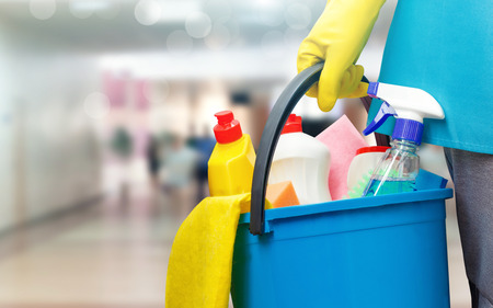 Cleaning lady with a bucket and cleaning products on blurred background. Stockfoto