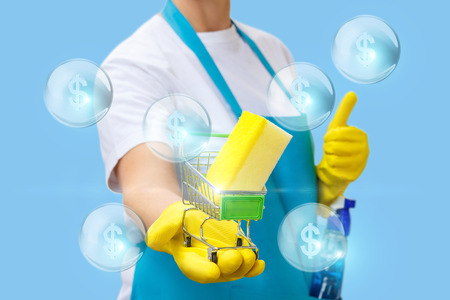 Cleaner in hand shows the shopping cart with a washcloth. Concept store household chemicals. Stock Photo