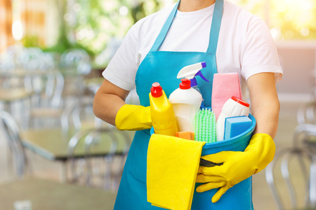 Cleaner with cleaning products in hand on blurred background.