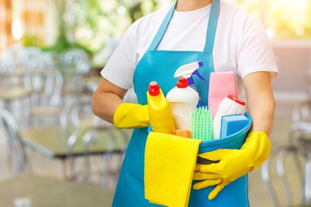 Limpiador con productos de limpieza a disposición en el fondo borroso. Foto de archivo - 89323541