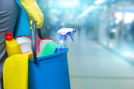 Cleaning lady with a bucket and cleaning products on blurred background .