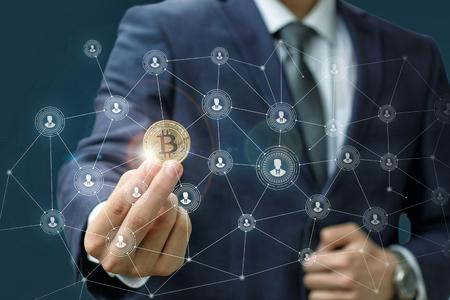 Zakenman houdt een bitcoin als onderdeel van een bedrijfsnetwerk op blauwe achtergrond. Stockfoto