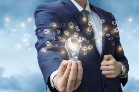 Light stays on in the hand of a businessman radiating gear. The concept of the idea as the business development.