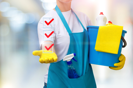 Cleaning lady shows a list of completed tasks on blurred background. Stock Photo