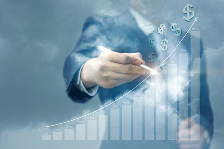 Businessman draws a graph of earnings growth against the sky. Stockfoto