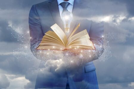 Businessman holding a book as a source of business ideas against the sky. Stock Photo