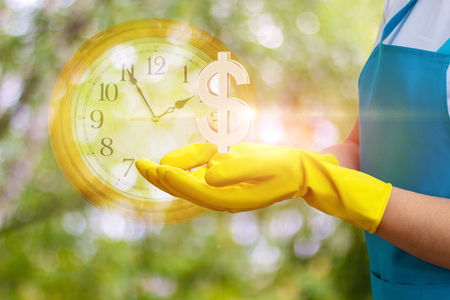 Cleaning lady shows a dollar sign. Concept time is money. Stock Photo