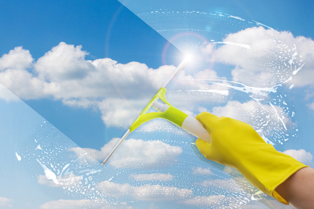Hand worker cleans a window on a sky background.