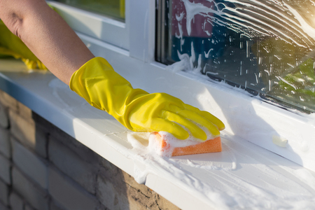Cleaner washes a window sill outside the house.