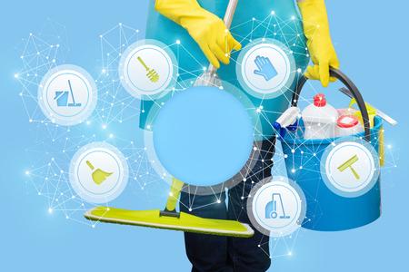 Schoonmaakster met een emmer en een MOP die de schoonmaakdienst op een blauwe achtergrond heeft. Stockfoto