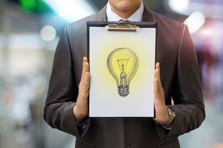 Light bulb drawn on a sheet in the hands of the businessman. Concept idea in the business. Foto de archivo