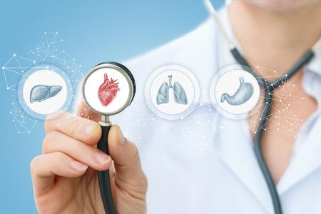 Arts luistert naar het hart op een blauwe achtergrond. Stockfoto