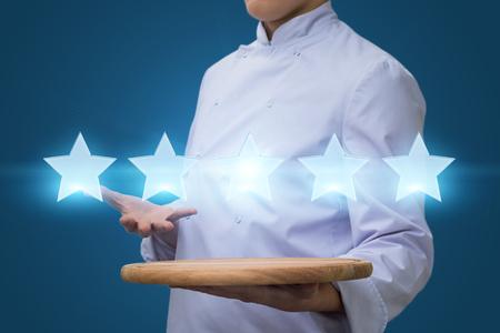 Cook muestra cinco estrellas. Concepto de calificación de restaurante Foto de archivo
